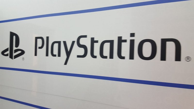 black Playstation logo and word on white wall