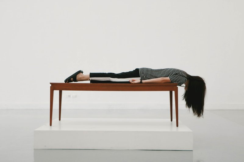 woman lying on a table with her head hanging off