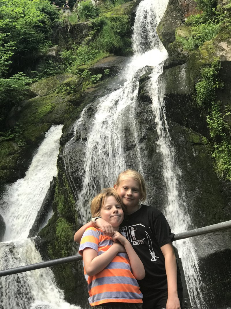 boys in front of waterfall in black forest