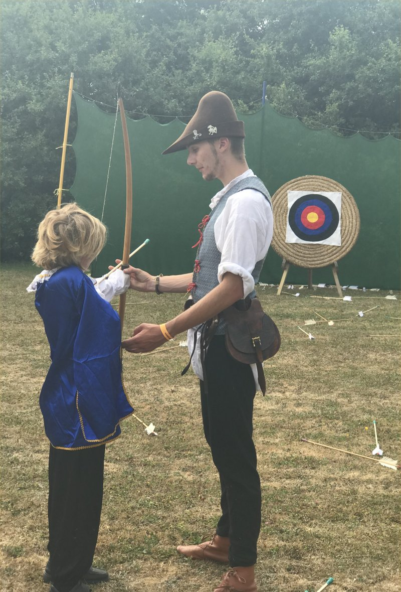 boy as musketeer doing archery