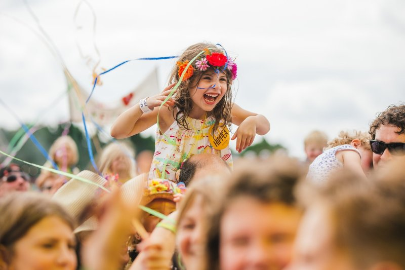 child lifted up in the crowd at a festival