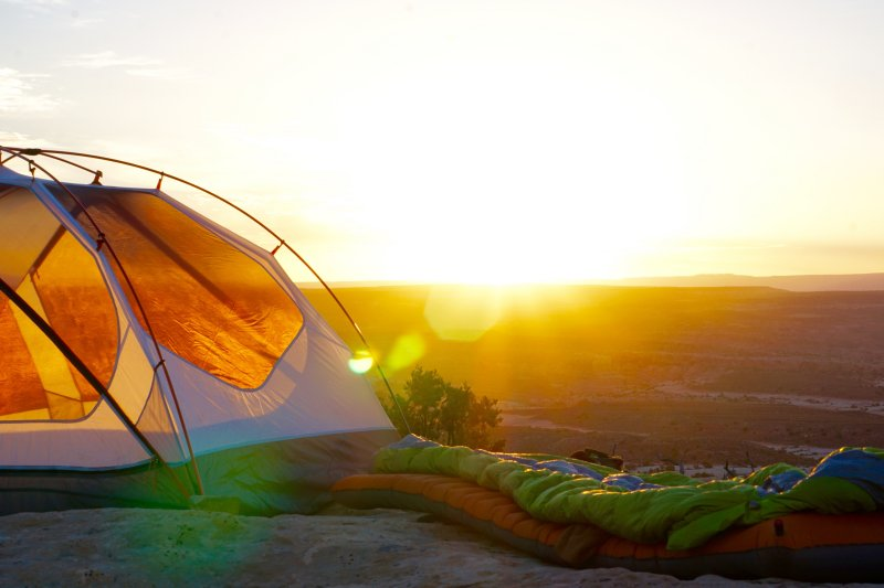 tent with sleeping bags outside as the sun rises