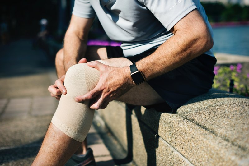 man gripping knee with bandage on